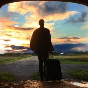 guy with suitcase walking away at sunset