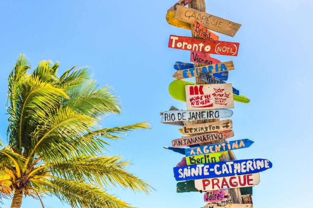 sign with locations to travel to and palm tree