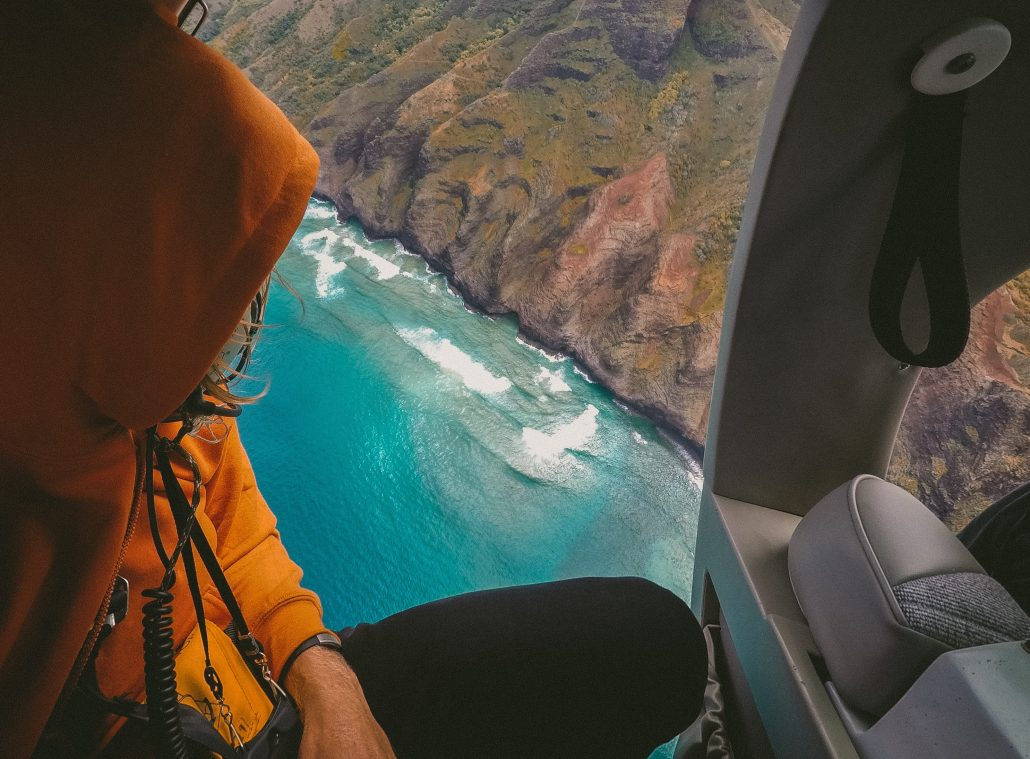 guy in helicopter over ocean and mountains unique experiences
