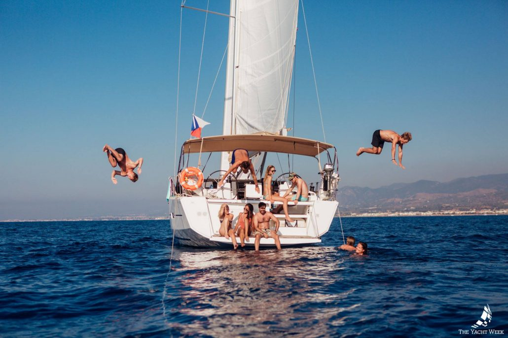 people jumping off sailboat on the yacht week