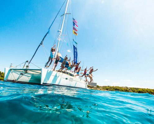the Yacht Week Greece catamaran with people jumping off