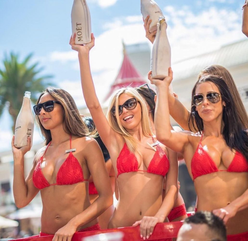 girls with moet champagne bottles at encore beach club