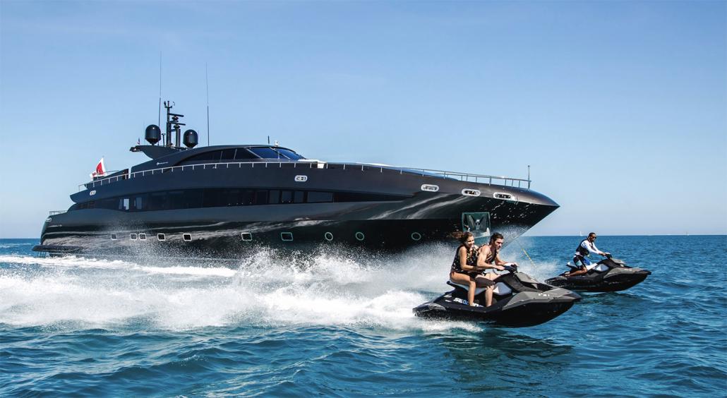 couple on jet skis next to luxury black yacht charter
