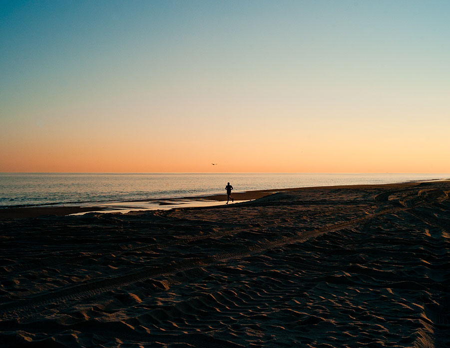 person running on beach at sunset in southampton