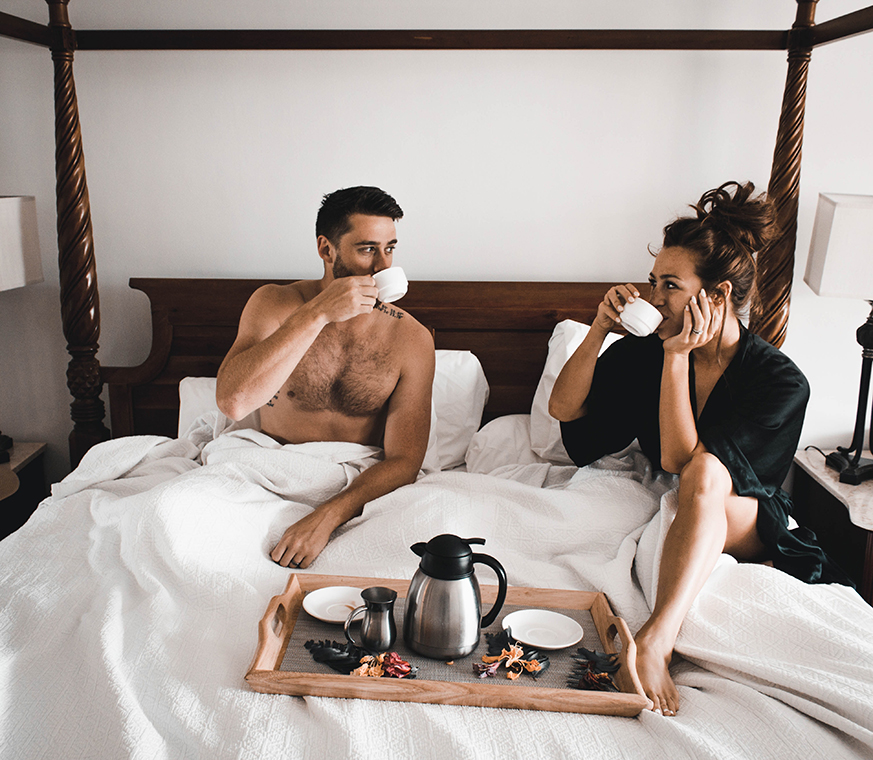 couple in bed on honeymoon having coffee